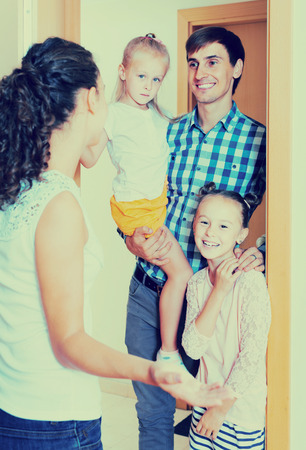 one on one meeting: smiling adults and kids meeting at doorway and greeting one another