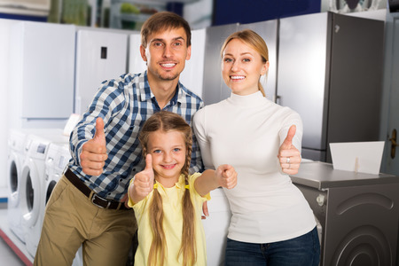 household appliance: portrait of cheerful family shopping in household appliance store