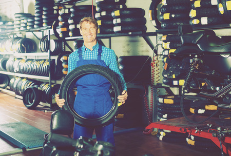 tire fitting: Positive working man standing with new tires for motorbike in hands in shop Stock Photo