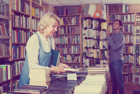 50s: portrait of mature woman 50s standing among bookshelves and looking for book Stock Photo
