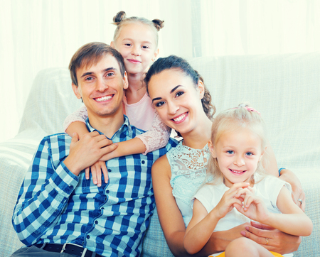 Portrait of cheerful young parents with two cute little daughters relaxing at home