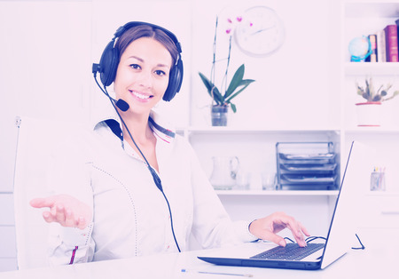 handsfree: Positive adult brunette woman talking with customer using hands-free set at call center