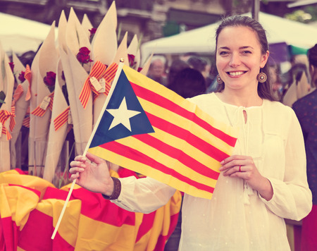 Happy woman with  Flag of Catalonia during Sant Jordi festival in Barcelona, Spain Stock Photo