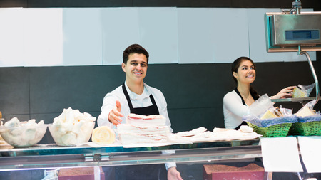 salo: Portrait of positive butchers offering salo and meat in shop Stock Photo