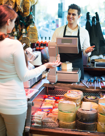 Young woman customer buying cheese for dessert in delicatessen store