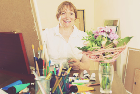 contentedness: Smiling senior woman painting a new picture