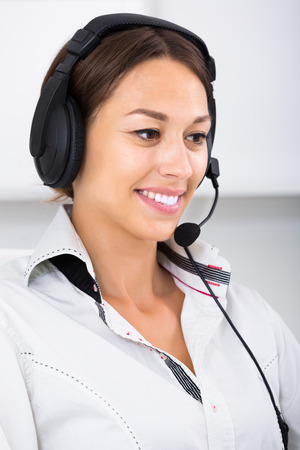 handsfree: Portret of happy young brunette woman talking with customer using hands-free set at call center