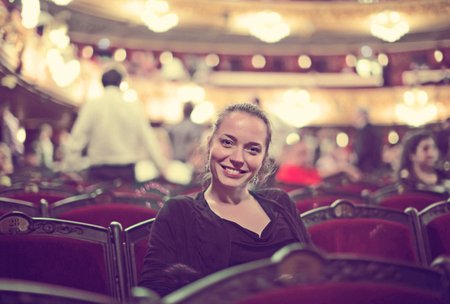 Portrait of happy woman in auditorium of opera teatre