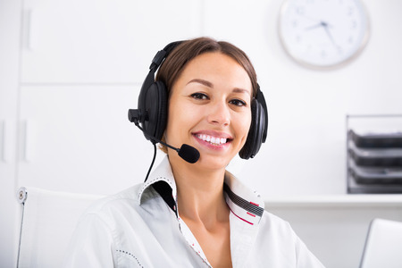 handsfree: Portret of positive adult brunette woman talking with customer using hands-free set at call center