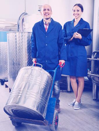 diligente: Retrato de mujer alegre experto diligente de pie con portapapeles y en�logo masculina en la secci�n de procesamiento de vino