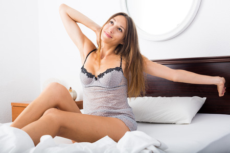 young woman in underwear sitting in bedroom in morning light and stretching her arms