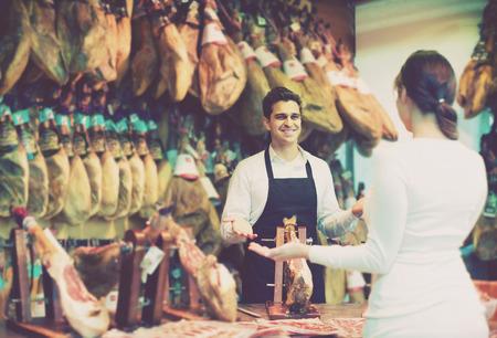 iberico: american brunette choosing iberico and serrano jamon and smiling Stock Photo