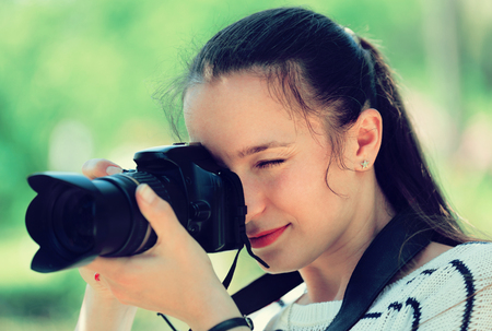 photocamera: Portrait of young positive girl with photocamera at park