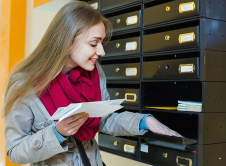outwear: Smiling happy girl in outwear receiving correspondence at hall entrance