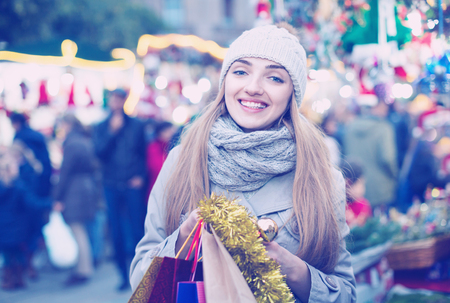 Portrait of young positive  woman in coat posing at Xmas fair in evening