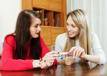 home pregnancy test: Happy women with pregnancy test at table in home