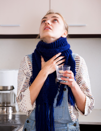 Young girl with quinsy taking medicine and gargling throat in kitchen