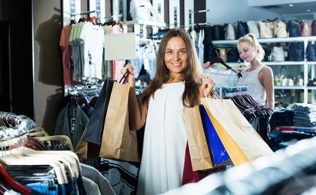 Porträt von fröhlichen Mädchen Brunette viele Einkaufstüten in der Modegeschäft halten