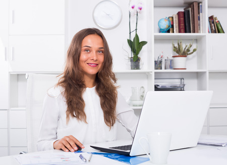 formalwear: Attentive young woman in formalwear sitting and working on laptop in company office