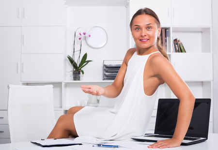 Smiling young woman relaxing on desk with documents in company office Standard-Bild