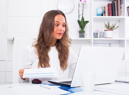 attentive: ?portrait of young attentive female employee having blank document in hands in office