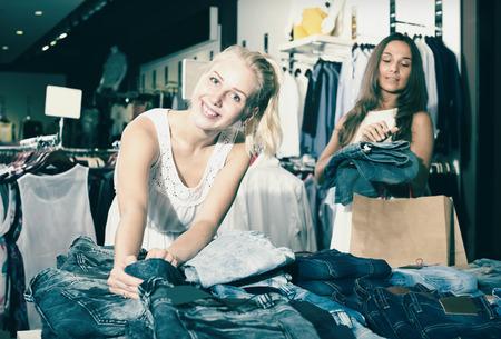 Zwei lachende Mädchen Denim-Hosen zusammen in Bekleidungsgeschäft Wahl