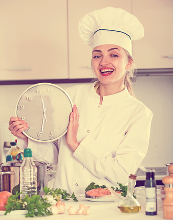 jorobado: Cheerful female in cook uniform with clock and fried salmon Foto de archivo