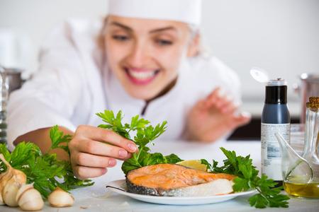 jorobado: cocinero americano joven feliz con salmón preparado en la cocina profesional. centrarse en los peces