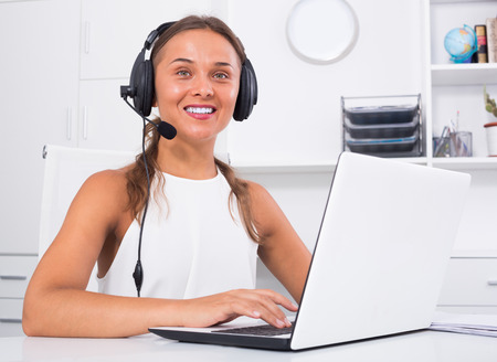 Happy young woman chatting with customer using headset at call center