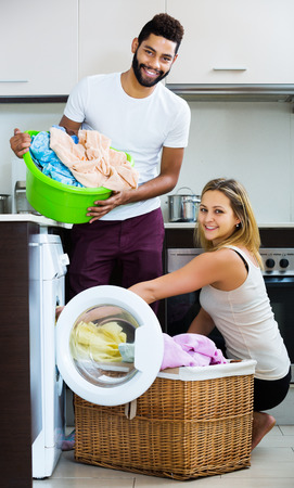 Happy young mixed spouses doing regular laundry and smiling at home