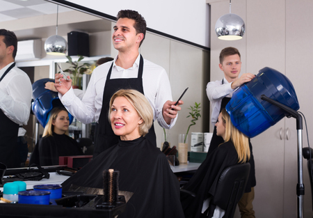 hairdressing saloon: Cheerful dark-haired man doing hairstyle for mature woman in hairdressing saloon Stock Photo