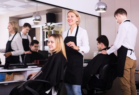 16s: Senior woman cuts hair of blonde girl in barbershop