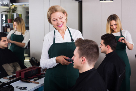 19's: Positive elderly hairdresser serving teenager in chair
