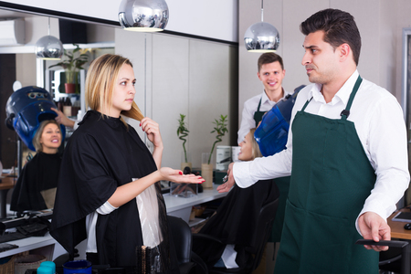 complaining: Young woman complaining on new haircut in hair salon