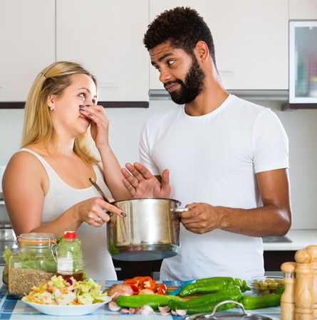 loathsome: White girl and black man smelling foul food inside Stock Photo