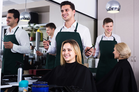 peignoir: Positive hairdresser cuts hair of blonde girl at salon Stock Photo