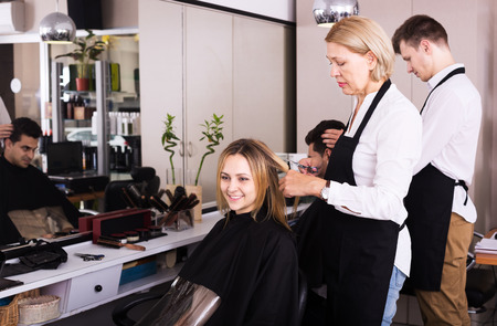 19's: Mature woman cuts hair of blonde girl at the hair salon Stock Photo