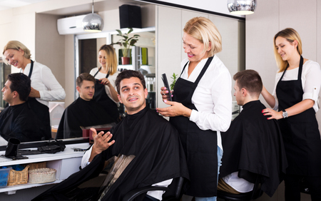 19's: Happy mature female doing hairstyle for adult man in hairdressing saloon Stock Photo