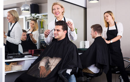 19's: Cheerful senior female doing hairstyle for adult man in hairdressing saloon. Focus on the man
