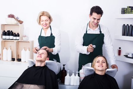 18's: Two smiling hairdressers working with hair of clients in washing tray. Focus on girl