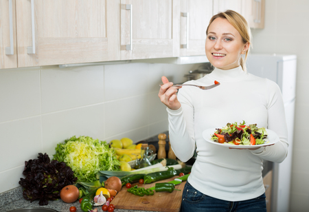 blondie: Cheerful young woman with plate of fresh salad at home