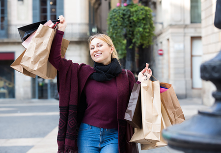 Happy smiling blond girl in jeans walking at the street and holding shopping paper bags Stock Photo