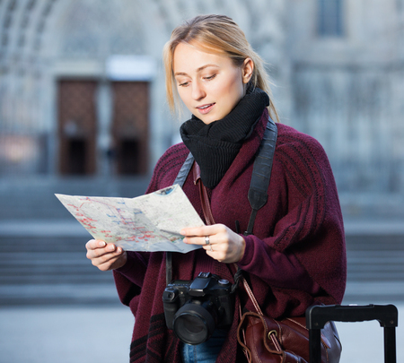 Young cheerful woman having a map and looking for her route in the city