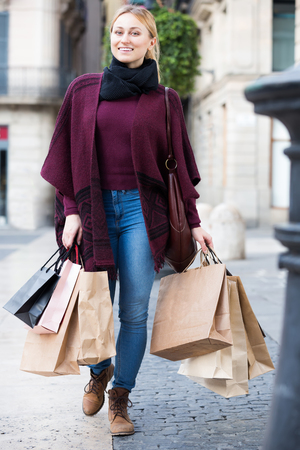 25 35: Joyful smiling blond girl in jeans carrying  shopping paper bags at the street