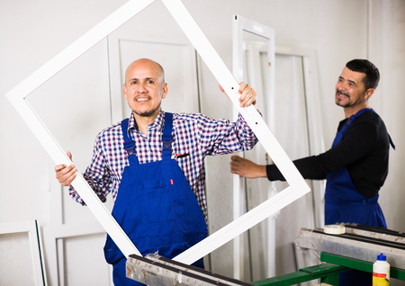 Professional workers with finished PVC profiles and windows at factory