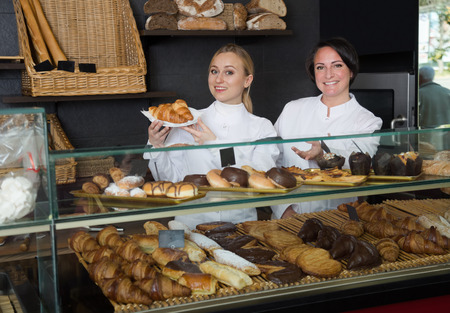 gladly: Smiling woman and young girl gladly selling pastry in the cafe