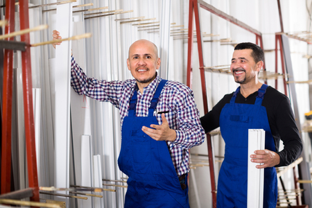 glasswear: Two cheerful workmen in blue coverall in workshop of PVC windows and doors . Selective focus Stock Photo