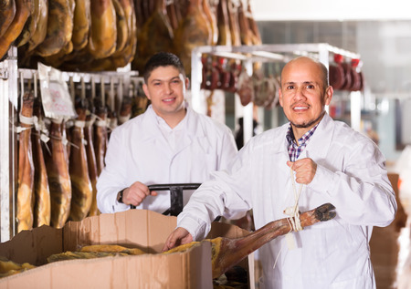 middle joint: Two farm workers in white overalls checking condition of serrano jamon joints
