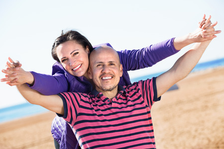 gladly: Positive charming mature couple gladly hugging each other and enjoying the beach