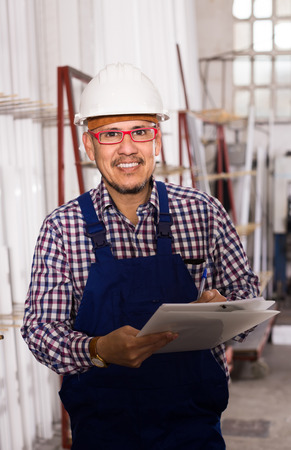 rigger: happy american male surveyor in coverall doing checkup and filling papers